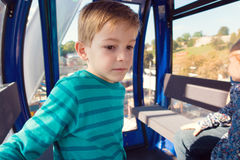 Cute little boy sitting in ferris wheel cabin at oktoberfest Royalty Free Stock Photography