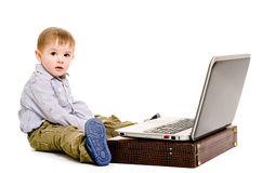 Cute little boy sitting on the floor with a laptop. Isolated Royalty Free Stock Images