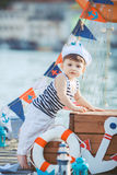 Cute little boy sitting on the floor on pier outdoor, a marine style. Little sailor Royalty Free Stock Image