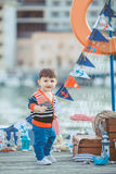 Cute little boy sitting on the floor on pier outdoor, a marine style. Little sailor Royalty Free Stock Photography