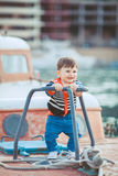 Cute little boy sitting on the floor on pier outdoor, a marine style. Little sailor Royalty Free Stock Images
