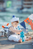 Cute little boy sitting on the floor on pier outdoor, a marine style. Little sailor Stock Photos
