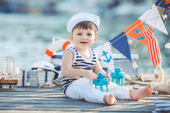 Cute little boy sitting on the floor on pier outdoor, a marine style. Little sailor Royalty Free Stock Photo