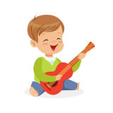 Cute little boy sitting on the floor playing guitar, young musician with toy musical instrument, musical education for Stock Images