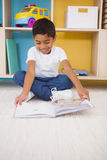Cute little boy sitting on floor reading in classroom Stock Photography