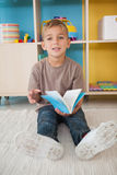 Cute little boy sitting on floor reading in classroom Royalty Free Stock Photo