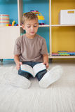 Cute little boy sitting on floor reading in classroom Royalty Free Stock Images