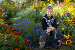 Cute little boy is sitting in the flower garden. Nature. Royalty Free Stock Photography