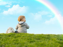 Cute little boy sitting on the green grass with a toy bunny Royalty Free Stock Images
