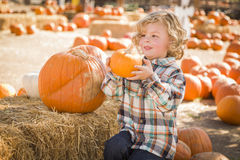 Cute Little Boy Sitting and Holding His Pumpkin at Pumpkin Patch Royalty Free Stock Image