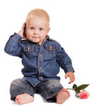 Cute little boy sitting holds mobile phone, rose isolated. Stock Photo