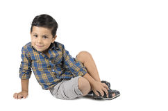 Cute little boy sitting isolated on white background. Royalty Free Stock Image