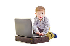 Cute little boy sitting with a laptop Stock Photos