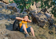 Cute little boy sitting on a mountain slope Royalty Free Stock Photo