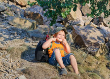 Cute little boy sitting on a mountain slope Royalty Free Stock Images