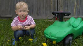 Cute little boy sitting near the green machine. In the yard of a country house stock images