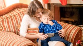 Cute little boy sitting on others lap in armchair and watching cartoons on smartphone. Little boy sitting on others lap in armchair and watching cartoons on royalty free stock photography
