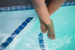 Cute little boy sitting poolside Royalty Free Stock Images