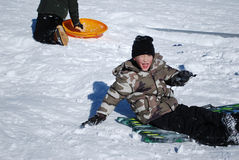 Cute little boy sitting on a sled in the snow. Stock Photos