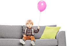 Cute little boy sitting on sofa with a balloon Royalty Free Stock Photo