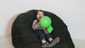 Cute little boy sitting on soft bag with ball. In his hands stock footage