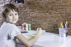 Cute little boy sitting at table and painting picture stock photography