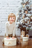 Cute little boy sitting under the Christmas tree with gift box Stock Photos