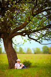 Cute Little Boy Sitting Under The Big Blooming Pear Tree, Countryside Stock Image