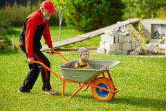 Cute little boy sitting in wheelbarrow Stock Image