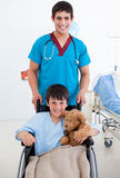 Cute little boy sitting on wheelchair and a doctor Stock Image
