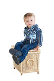 Cute little boy sitting on wicker basket Royalty Free Stock Photos