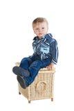 Cute little boy sitting on wicker basket Royalty Free Stock Photos