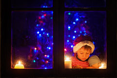 Cute little boy, sitting on a window at night, looking outdoors, Stock Photos
