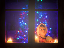 Cute little boy, sitting on a window at night, looking outdoors, Stock Photo