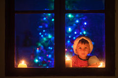 Cute little boy, sitting on a window at night, looking outdoors, waiting for Santa Claus and Christmas stock photos