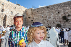 Cute little boy in skullcap and his older brother. Cute little boy in a skullcap and his older brother seven years. They cost at Western Wall of Temple. The Royalty Free Stock Image