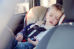 Cute little boy sleeping in car. Seat Stock Photo
