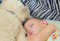 Cute little boy sleeping with his teddy bear Royalty Free Stock Photos
