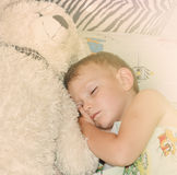 Cute little boy sleeping with his teddy bear Stock Photos