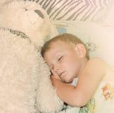 Cute little boy sleeping with his teddy bear Stock Photos