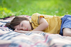 Cute little boy, sleeping on a picnic blanket, outdoors in a sum. Mer sunny afternoon Royalty Free Stock Images