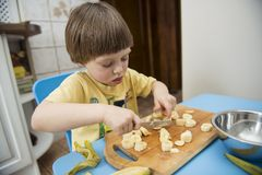 Little chef. Cute little boy slicing bananas stock photography