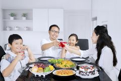 Little boy toasting glasses with his family. Cute little boy smiling at the camera while toasting glasses with his family and having meals in the kitchen stock photo