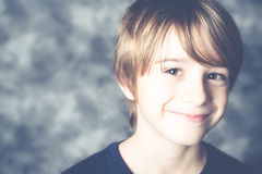 Cute little boy smiling on gray background Royalty Free Stock Photos