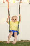 Cute little boy smiling and playing on outdoor swings Stock Photography