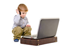 Cute little boy speaks on a mobile phone looking at laptop. Isolated Royalty Free Stock Images