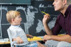 Cute little boy at speechtherapist session. Royalty Free Stock Image