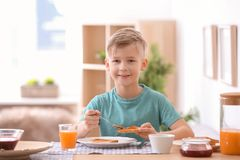 Cute little boy spreading jam onto tasty toasted bread. At table stock images