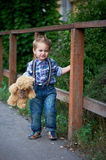 Cute little boy standing near a brown wooden , stylish jeans with suspenders and plaid shirt . Memories of childhood. And carefree Stock Photos