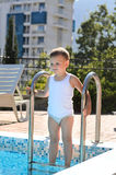 Cute little boy standing on swimming pool steps. As he contemplated the cool water on a hot summer day with a smile of anticipation Royalty Free Stock Photography
